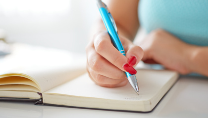 Young woman writes to black diary