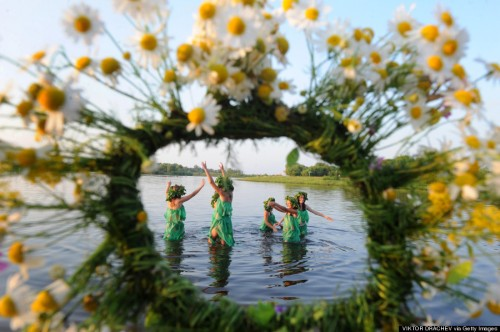 Belarussian girls wearing homemade grass-skirts dance in a river while celebrating Ivan Kupala Night, a traditional Slavic holiday, 270km south of Minsk in Turov on July 6, 2012. During the celebration, which finds its origin in pagan times, people plait wreaths, jump over fires, and swim. AFP PHOTO / VIKTOR DRACHEV        (Photo credit should read VIKTOR DRACHEV/AFP/GettyImages)